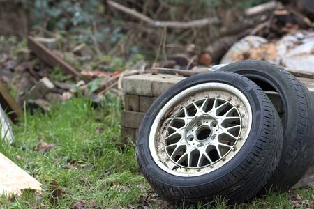 Dumped car tyres. Fly-tipping old tyre waste and rubber recycling. Two vehicle tires discarded illegally.