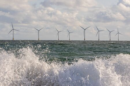 Wind and wave energy. Breaking waves with offshore windfarm turbines background. Sustainable resource and renewable energy. Dynamic power industry image. Banco de Imagens