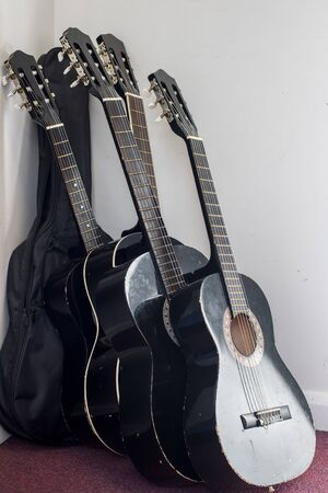 Five black classical guitars leaning against the wall. Student acoustic guitars badly stored in music room.