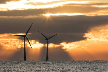 Dramatic sky. Solar and wind power. Offshore turbines at sunrise. New dawn over the sea horizon. Spiritual and environmental conservation image from Norfolk UK. Archivio Fotografico