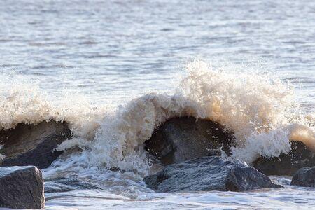 Sea flood defence. Waves crashing on rocks. Coastal erosion, climate change and rising sea level. UK coast at risk from global warming.
