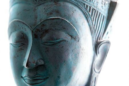 Blue Buddha face. Spiritual lifestyle close-up. Soft selective focus image of contemporary Buddhist head statue on white background. Serene expression of tranquility, meditation and mindful devotion. Stock Photo