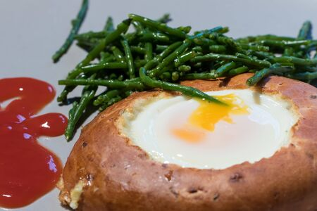 Healthy cooked breakfast meal. Egg in bagel hole with samphire with tomato ketchup. Unusual combination for healthy eating. Close up food presentation.