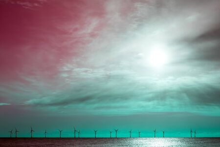 Green energy fighting global warming. Surreal pink red and green sky wind turbine border image. Electricity turbines on the horizon. Soft pastel color background landscape image.  Archivio Fotografico