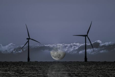 Nighttime electricity generation. Offshore wind turbines with moon at night representing 24hr clean energy production from sustainable resource wind power. Constant renewable energy throughout the day