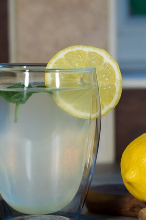 Fresh lemonade. Glass of authentic home-made lemon drink with mint and a slice of organic lemon. Thirst-quenching healthy summer beverage in close-up.