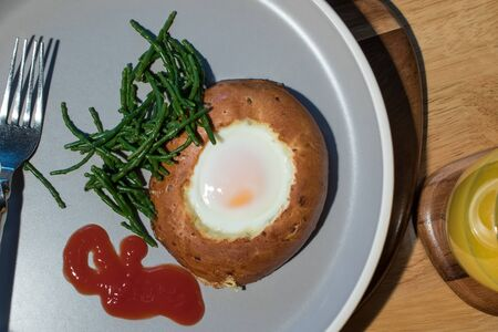 Egg in a bagel hole with samphire. Simple healthy breakfast meal. Close-up flat-lay image of brunch with tomato ketchup.