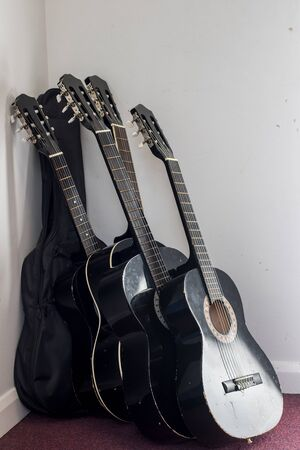 Stack of used classical acoustic guitars in storage. Guitars leaning on music room wall. Five acoustic guitars only one in a case. Stock Photo