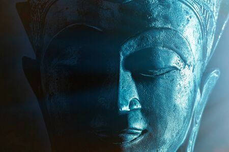Spiritual enlightenment. Mindful Buddha face close-up with ethereal blue light. Mysticism and spirituality portrayed in calm close up image of peaceful buddhist meditation. Serene divine devotion