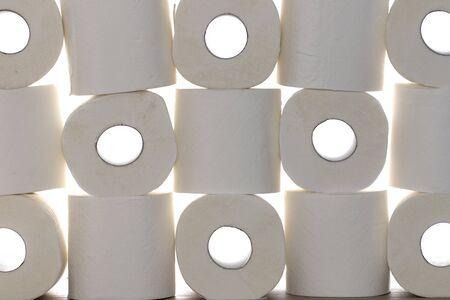 Toilet paper background image. Stack of loo rolls against white background. Coronavirus covid-19 mass panic buying item. Multiple rolls of generic toilet tissue.
