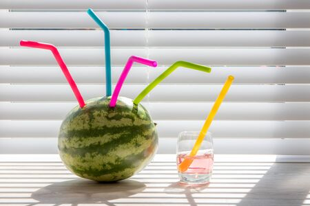 Watermelon summer juice drink. Fun colorful silicon straws in fruit. Healthy refreshing drink with funky environmentally friendly reusable straws. Summer day thirst quenching treat. Stock Photo