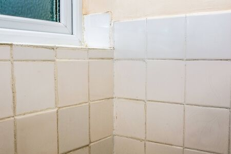Bad tiling. Terrible bathroom tile DIY fixing and grouting job. Old white ceramic tiles with untidy grout after do-it-yourself or rogue trader disaster. Job for a professional home tiler tradesperson