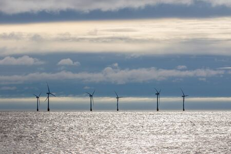Clean energy. Offshore wind farm turbines on sea horizon with cloudscape background. Blue sky and clouds behind silhouetted wind power turbines. Crisp calm morning weather. Stock Photo