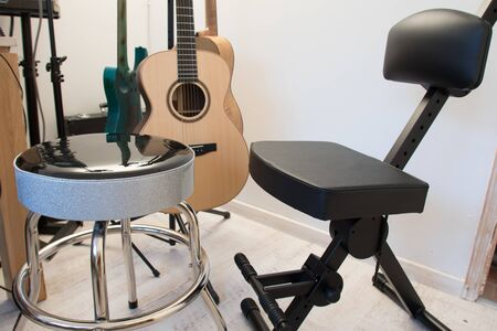 Guitar seat and stool in a music practice room. Musicians chair with back rest and foot rest.