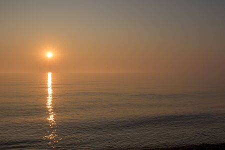 Beautiful misty morning sunrise over a calm sea. Soft sky and distant wind turbines with bright sunlight reflecting off the water. Gorgeous calm and peaceful seascape representing hope and tranquility