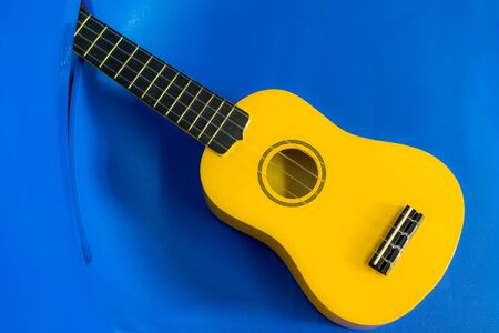 Yellow ukulele. Child uke on a blue plastic kids chair background. Musical instrument for children. Brightly colored ukulele for fun music play.