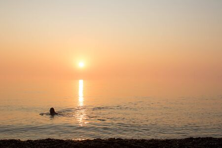 Healthy lifestyle swimmer. Misty morning swim in the sea. Elderly man or woman doing Covid19 isolation exercise. Going to work maintaining social distance, avoiding public transport and staying safe