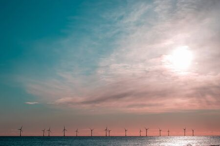 Sustainable resource. Offshore wind farm turbines on the sea horizon. Renewable energy background image with beautiful fresh morning sky copy space. Lower border of wind power electricity turbines