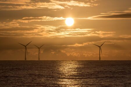 Morning has broken. Offshore wind farm sunrise beautiful religious or spiritual background image. Full sun reflecting off a calm sea. Peaceful tranquil scene of global warming, climate change and environmental conservation.