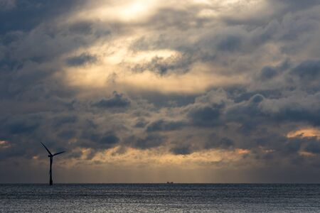 Dark dramatic sky over sea horizon landscape with wind turbine silhouette. Skyscape background image with backlit clouds over calm ocean water. Beautiful stark cloudy sky at sunrise or sunset