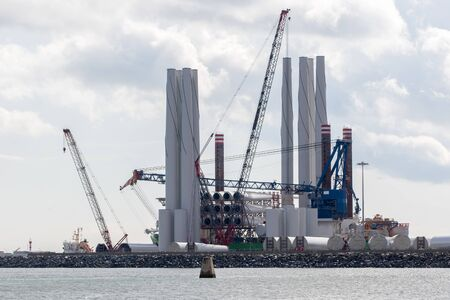 Renewable energy offshore windfarm wind turbine construction industry. Turbine parts at Great Yarmouth outer harbor UK. Investment in clean energy and alternative electricity generation.