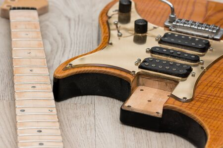 Electric guitar repair. Close-up of neck removed from body for refinishing. Preparation for fret dressing and finish work on this battered instrument. Stock Photo