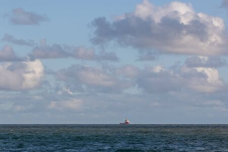 Ship on the horizon. Seascape with cloudy blue sky over distant boat at sea Standard-Bild