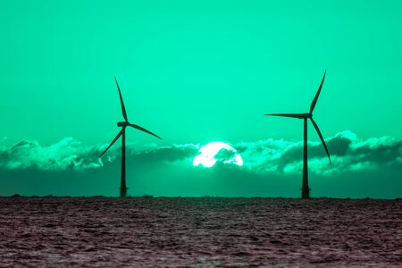 Green energy. Wind and solar power fighting global warming. Sustainable resources. Beautiful toned sky sunrise behind silouette of wind turbines on soft sea horizon. Clean renewable energy.