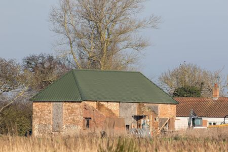 Barn conversion project, Renovation of farm building in progress. Rural brick built barn outbuilding being converted. Construction work renovating a country farmhouse barn with green corrugated roof.