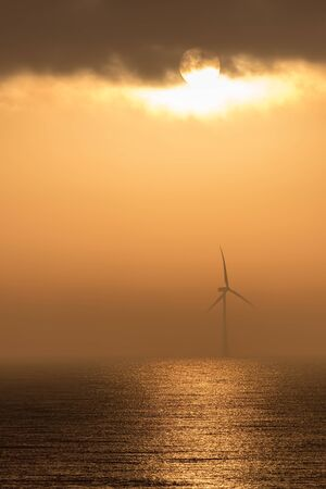 Misty morning sunrise over the sea with offshore wind turbine. Orange sky representing climate change and global warming. Solar and wind energy. Beautiful background image with copy space.
