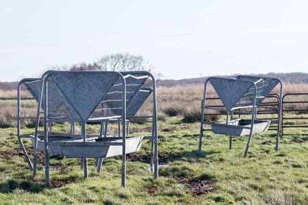 Metal cattle feeder and troughs. Old used hayracks and mangers in a muddy agricultural field. Cow feeding station on an English farm Norfolk UK Standard-Bild