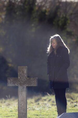 Grieving woman in black. Mourning lady at grave in cemetery. Middle-aged to elderly woman at graveside cross on a cold misty hazy autumn morning.