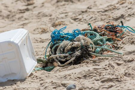 Plastic and commercial fishing rope and net pollution on a beach in Norfolk UK. Fishing net and line tangled and washed up on the shore. Marine pollution that is a danger to wildlife. Standard-Bild