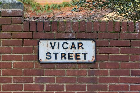 Vicar Street sign. Religious career path. Road leading to the church manse. Spiritual direction of an English town place name fixed to a red brick garden wall in a UK village. A pious life of devotion Standard-Bild