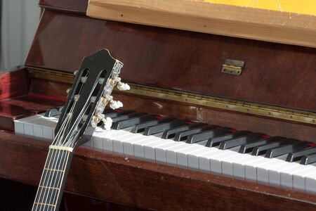 Classical music. Acoustic guitar resting on an old piano. Music teachers teaching music,practice room close-up.