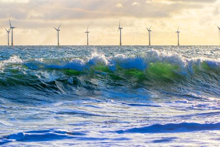 Green energy. Wind power and wave energy. Renewable sustainable resources from offshore wind farm turbines on the sea horizon. Environmental conservation for climate change and global warming. Imagens