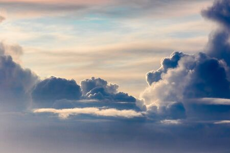 Beautiful cloudscape background image. Real low bank of dark clouds with blue sky and hazy cloud above. Natural photographic graphic resource of low border stormy weather with a sunny break on top. Standard-Bild
