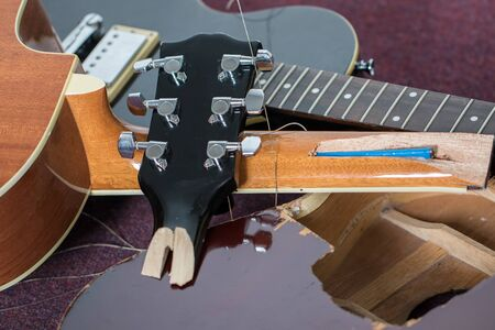 Smashed guitars. Pile of broken electric and acoustic guitar bits. Close-up of damaged musical instruments including headstock, neck and body of various guitars. Frustrated guitarist.