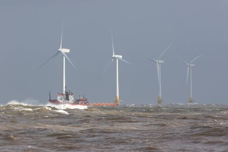 Ship on rough sea horizon by offshore wind farm turbines. Safety standby rescue and maintenance vessel on ocean waves. Alternative energy and wind power industry construction and development image