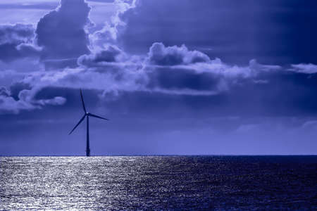 Solitary offshore wind farm turbine by moonlight Blue tone energy image with wind turbine on the sea horizon at night. 24hr clean energy production from sustainable resources Constant renewable energy