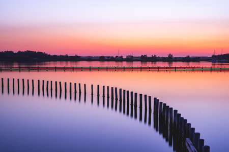 Beautiful sunset with a colorful sky. Grote Piet Zeeland, The Netherlands 스톡 콘텐츠