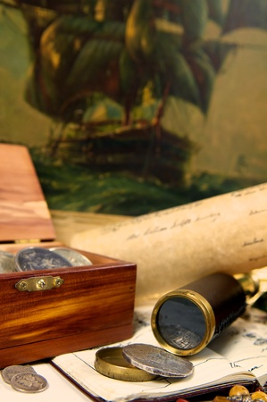 An adventurous scene of treasure and exploration  Filled with maps, spanish silver, and a trusty telescope  Could this be desk of a captain, or a pirate perhaps  photo
