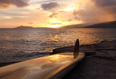 Vintage surfboard on rocky shoreline on Southern Oahu coast in Hawaii