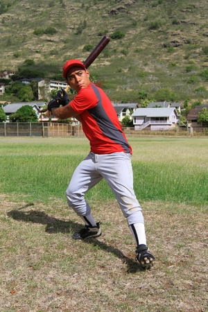 Baseball player prepares to swing in an open grassy field Stock Photo
