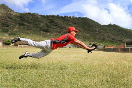 Baseball player dives to catch a stray ball