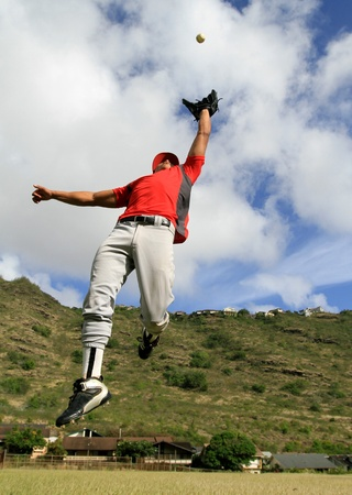 outfield: Baseball player jumps to catch a fly ball