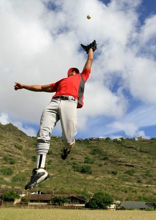 coger: El jugador de b�isbol salta para atrapar una bola de fly