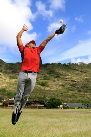 atrapar: El jugador de b�isbol salta alto para atrapar una pelota