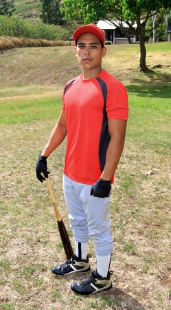 Baseball player poses with his equipment