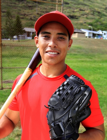 Baseball player smiles with his glove and bat